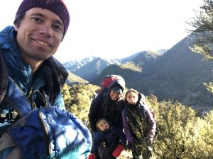 Man and lade with their children walking through the mountains