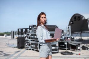 Woman standing with laptop in front of black boxes full of equipment to setup at a concert